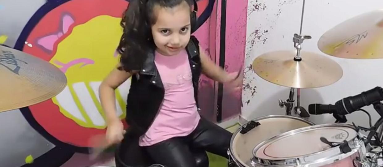 6-latka gra Slipknota na różowej perkusji