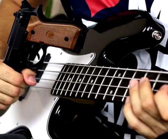 Guns N' Roses zagrany bronią i różą na basie