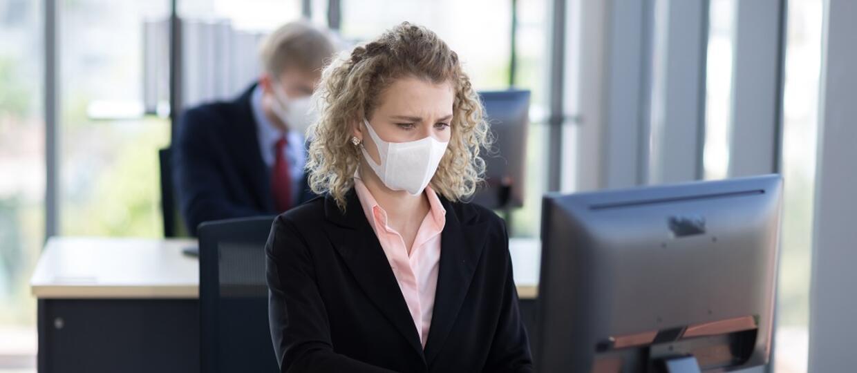 osoby pracujący przy biurkach w maskach