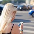 kobieta ze smartfonem na przejściu dla pieszych