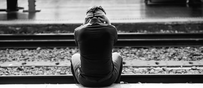 przygnębiony młody człowiek na peronie