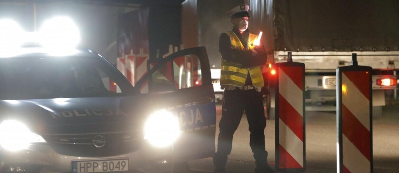 policjant w maseczce przy radiowozie w nocy