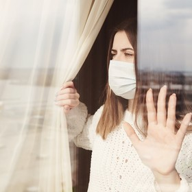 kobieta w maseczce wygladająca przez okno