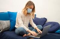kobieta w maseczce w domu przed komputerem