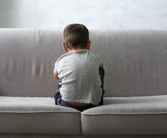 odwrócone tyłem dziecko siedzące na kanapie