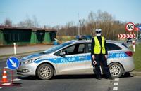 policjant w masce ochronnej przy radiowozie
