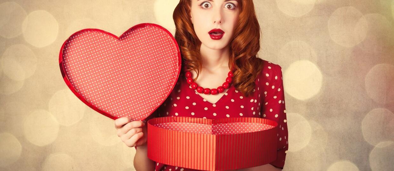 ruda dziewczyna z otwartym prezentem w pudelku w kształcie serca