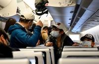 pasażerowie samolotu w maskach przeciwko koronawirusowi