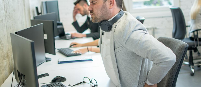 mężczyzna z bólem pleców przed komputerem