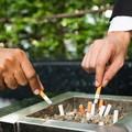 dwóch mężczyzn palących przy popielniczce