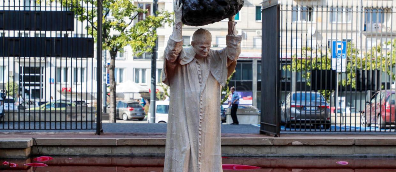 Rzezba przestawiajaca papieza Jana Pawla II rzucajacego glazem do basenu wypelnionego czerwona ciecza