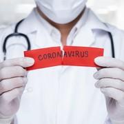 lekarz z kartką o koronawirusie