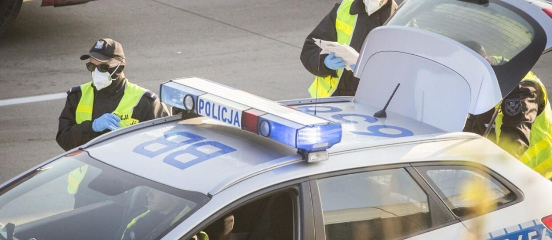 policjanci w maskach ochronnych przy radiowozie