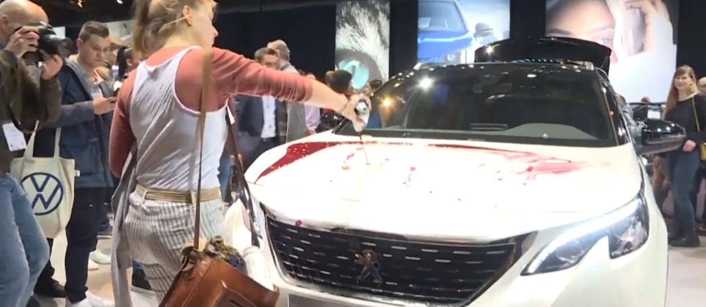 działaczka rozlewajaca sztuczną krew na samochód