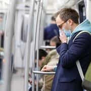 mężczyzna w masce jadący metrem