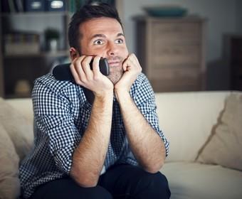mężczyzna oglądający telewizję z pilotem w ręce